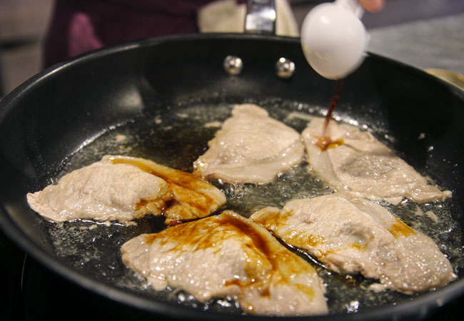 片面が焼けたら肉を裏返し、全体に砂糖をまぶし、中火にします。